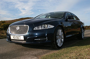 Navy blue chauffeur-driven Jaguar